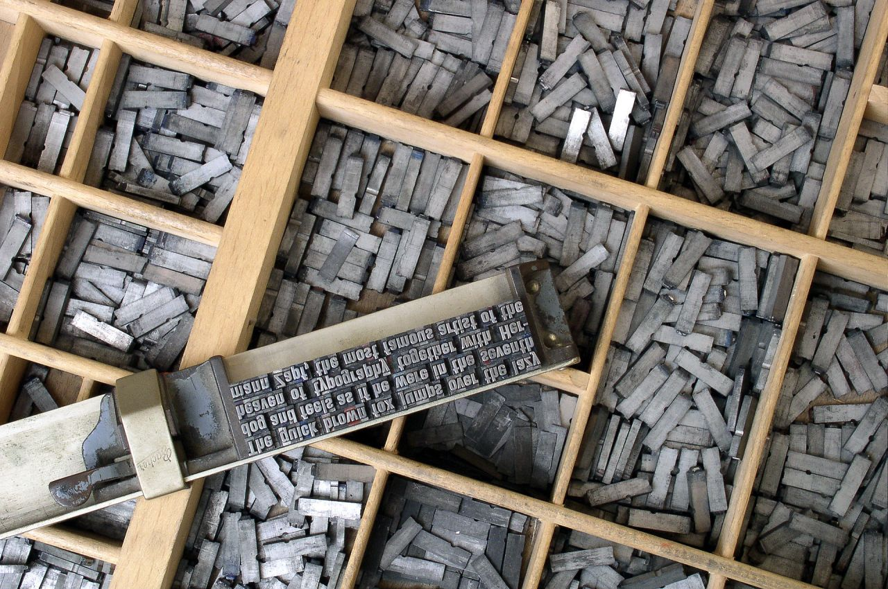 "Moveable type on a composing stick in front of a type case. It reads, ""The quick brown fox jumps over the lazy dog and feels as if he were in the seventh heaven of typography together with Hermann Zapf, the most famous artist of the"""
